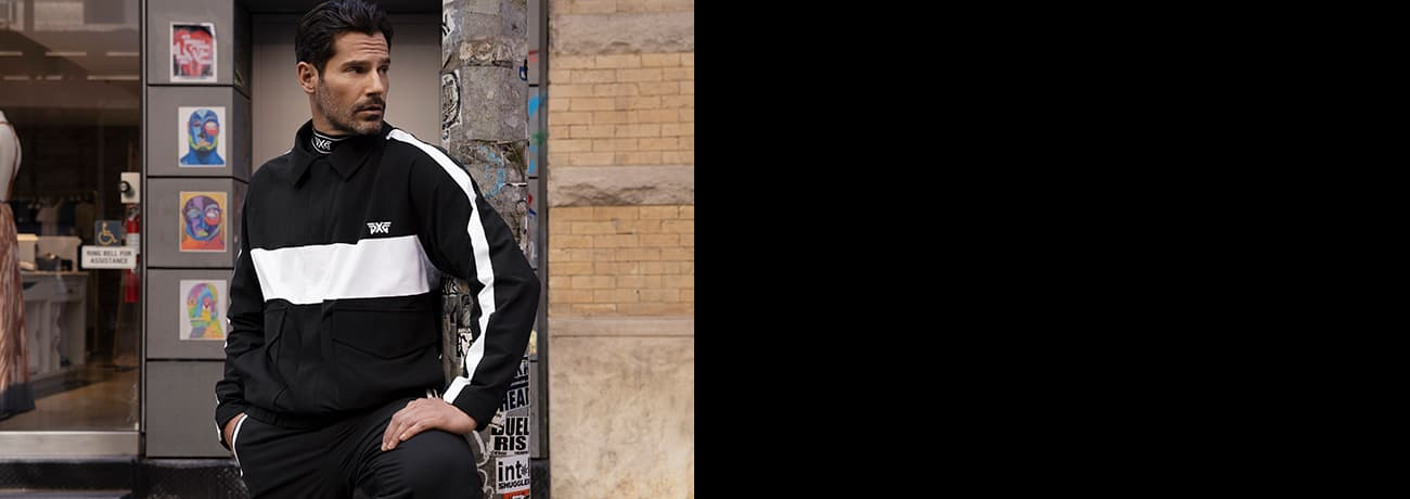 Man Standing Wearing PXG Apparel Mock Neck, Striped Bomber Jacket, & Golf Pants | PXG