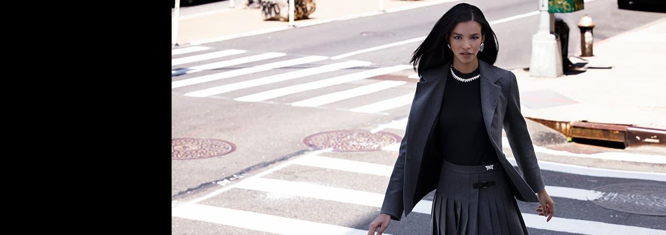 Women Crossing Street in PXG Blazer, Cashmere Mock Neck Shirt, Gray Pleated Skirt   PXG