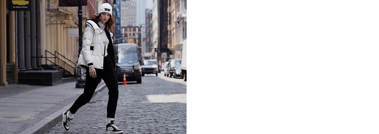 Women Crossing Street in White PXG Jacket, Fairway Camo Long Sleeve Top & Black Joggers