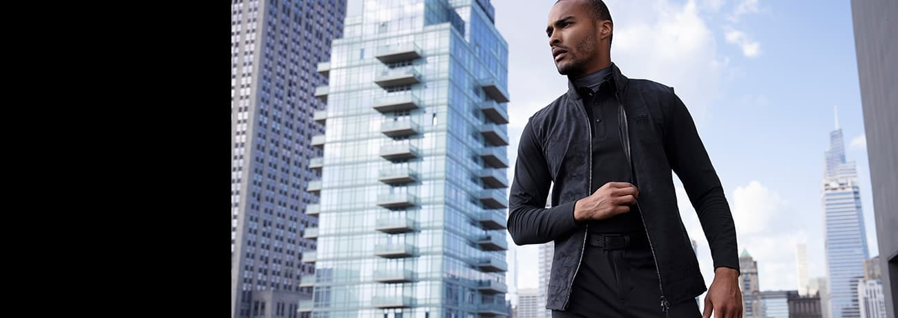 Man in City Wearing PXG Apparel Gray Long Sleeve Polo, Short Sleeve Mock Neck, Golf Pants & Belt | PXG