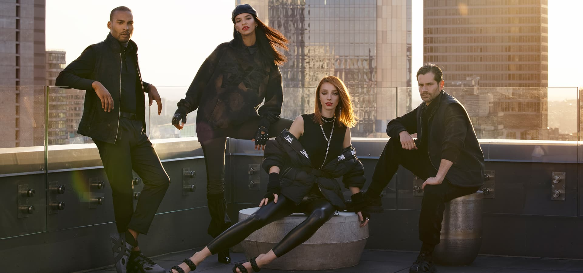 Four models, two male and two female sitting on a New York City rooftop, wearing PXG apparel.