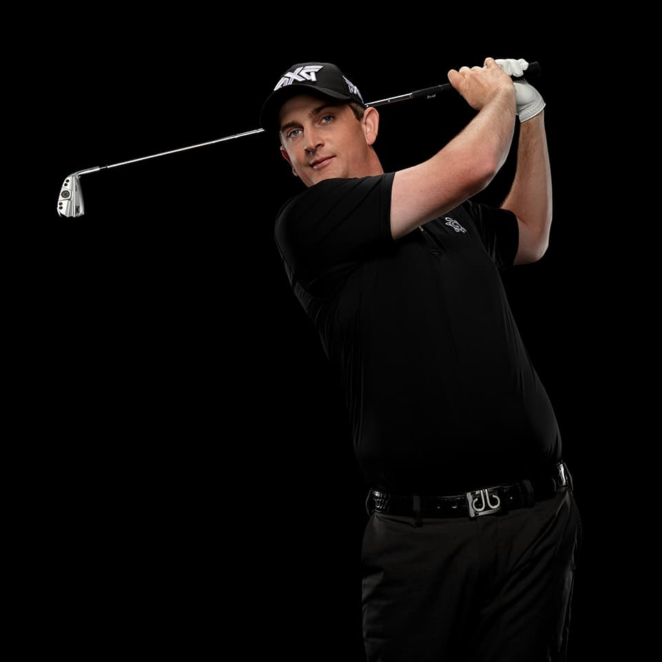 PXG TOUR Pro Henrik Norlander swinging a golf club in a studio.