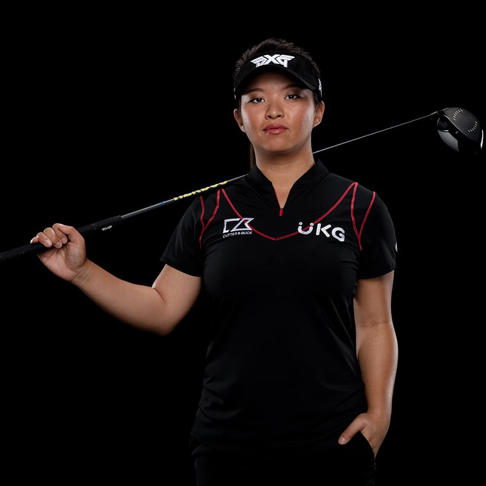 PXG TOUR Pro Megan Khang posing with a golf club in a studio.