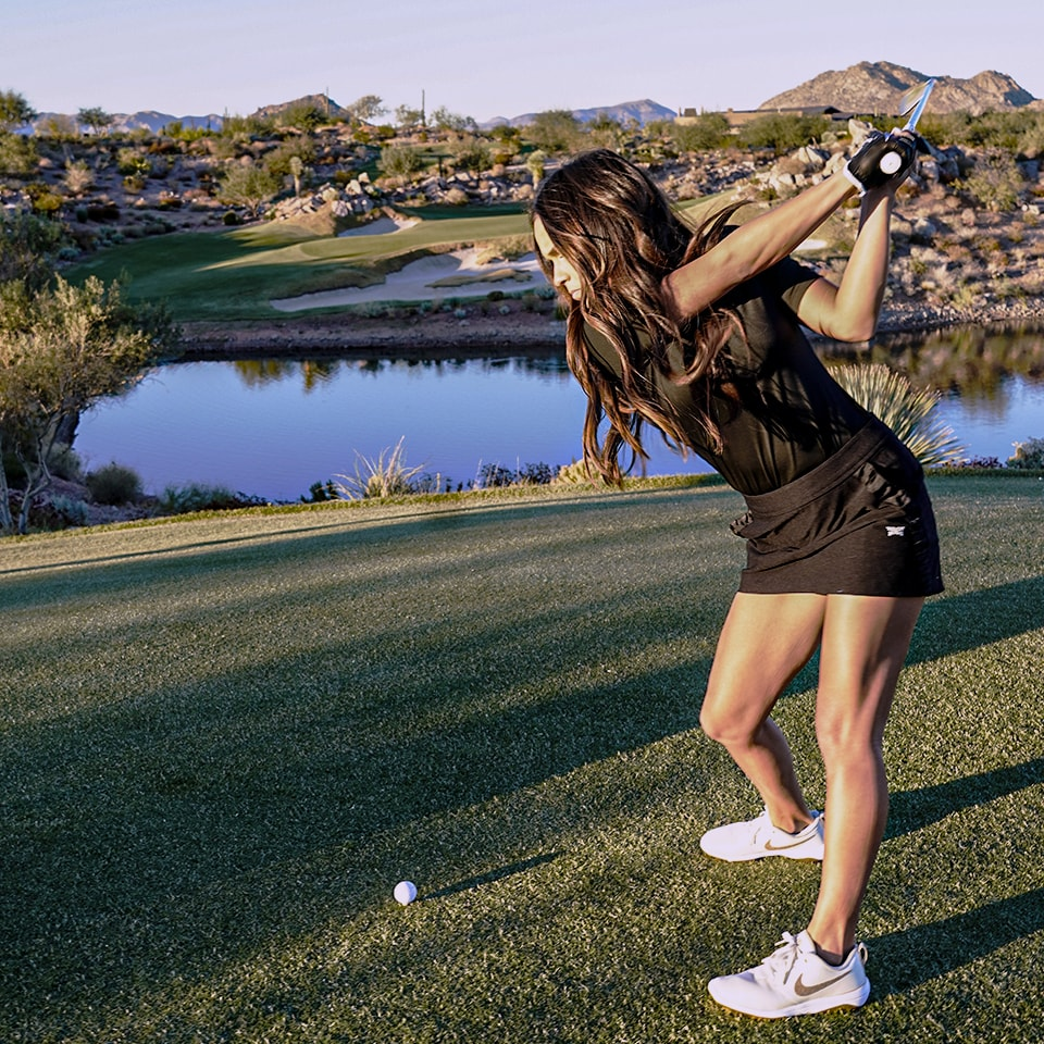 Female left handed golfer teeing off with a seven iron.