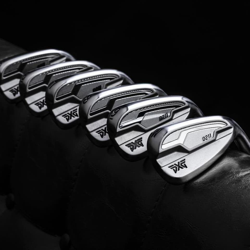 A set of PXG 0211 irons leaning on a leather couch.