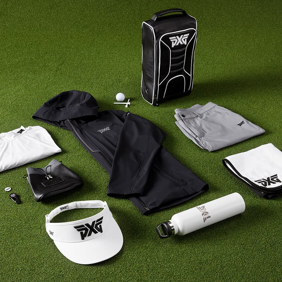 A collection of PXG apparel and accessories on a golf putting green