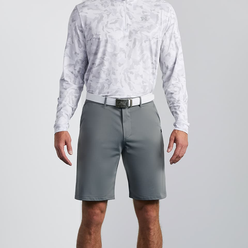 Model wearing a pair of men's PXG golf shorts in grey
