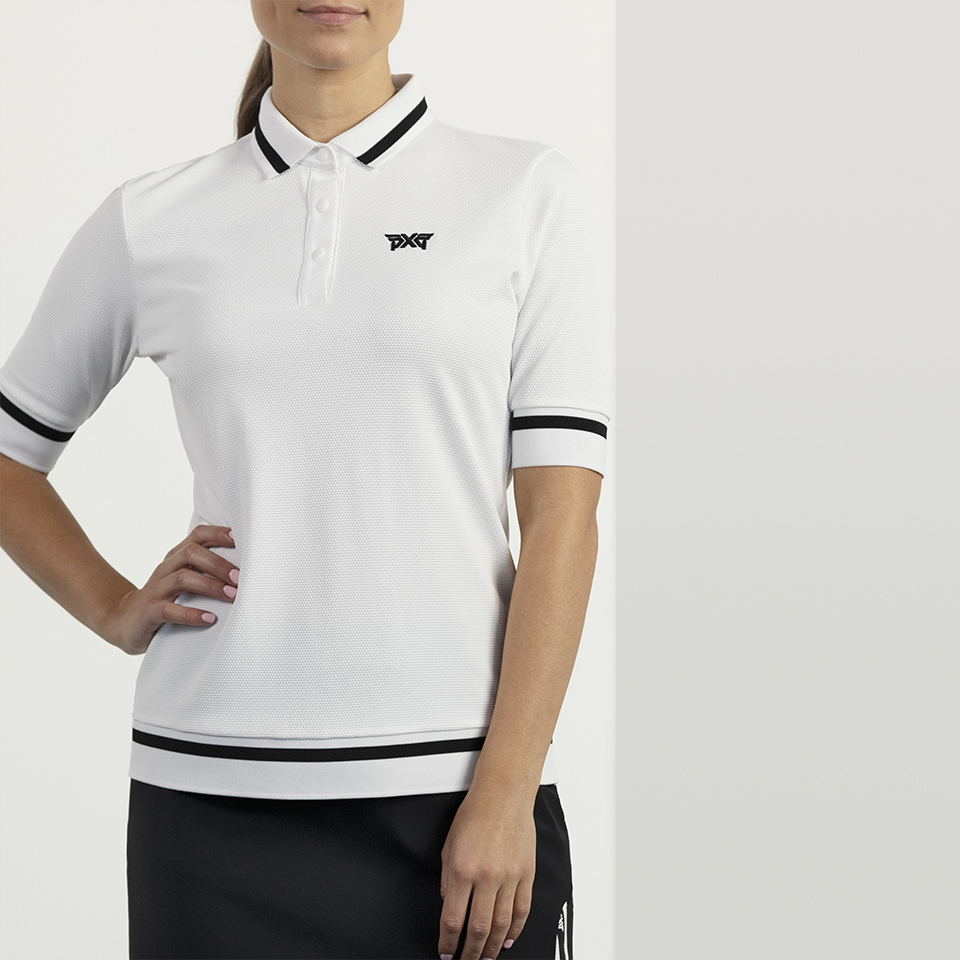 Model wearing a PXG contrast sleeve polo in white with black accents