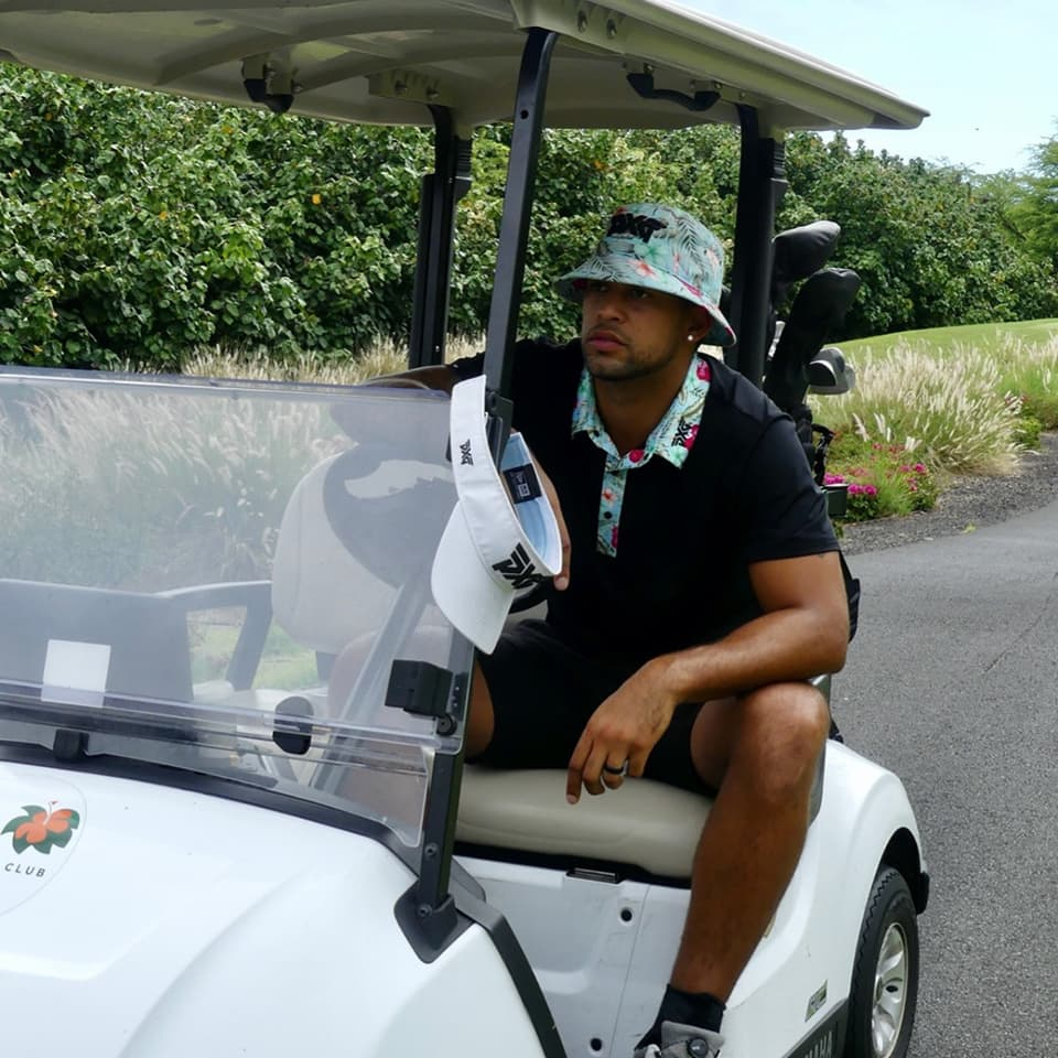 Gentleman sitting in a golf cart wearing a floral bucket hat and black polo with a floral collar.